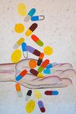 Male hand catching falling pills — Stok fotoğraf