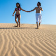 Beautiful and happy young couple walking in the sand — Stock Photo #45042939