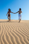 Beautiful and happy young couple walking in the sand — Stock Photo