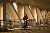 Woman cycling under a bridge with French taste — Stock Photo