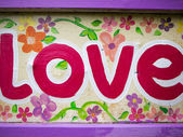 Word love painted on a wooden information board  — Stock Photo