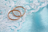 Wedding rings over blue backgound — Stok fotoğraf
