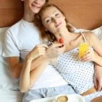 genç bir çift yatakta kahvaltı var — Stok fotoğraf