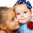Stock Photo: Big sister and little sister kissing