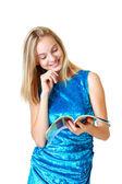 Beautiful happy blond teenage girl looking on journal — Stock Photo