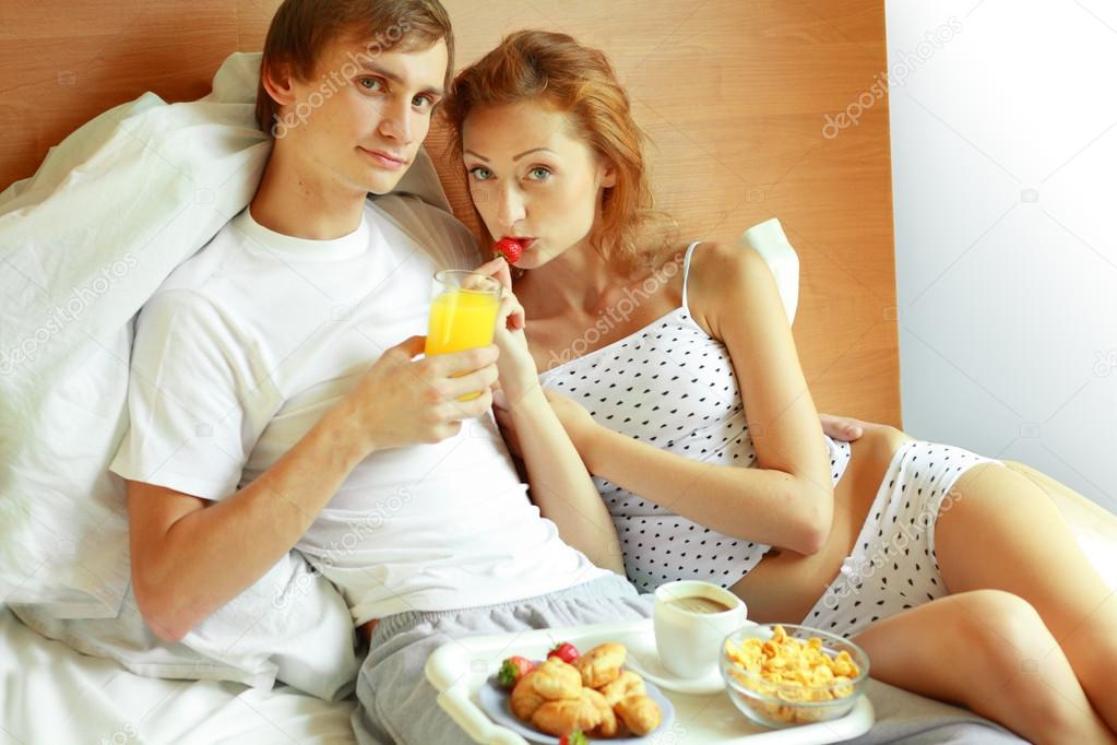 Relaxed young couple lying on bed comfortably with served breakfast in foreground — Photo #17652167