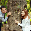 Young couple being playful around the tree — Stock Photo