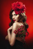 Woman with red flowers in hair — Stock Photo