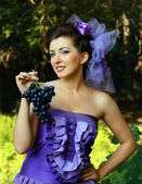 Woman in violet fashion dress grapes — Stock Photo