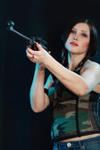 Beautiful woman holding weapon — Stock Photo