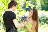 Man presenting blue flowers to a woman — Stock Photo