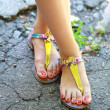 Feet wearing summer sandals — Stock Photo