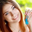 Young woman holding up a set of keys — Stock Photo #31246065