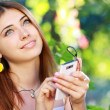 Stockfoto: Young womusing smartphone to listen to music