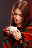 Woman in a blanket with cup — Stok fotoğraf