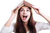 Girl with book over her head — Stock Photo