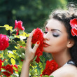 Woman smelling red roses — Stock Photo #48141157