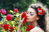 Mulher cheirando a rosas vermelhas — Fotografia Stock