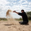The guy throws sand — Stock Photo