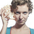 Girl with a sea shell to your ear — Stock Photo #19861333