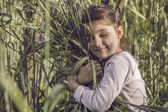Girl tenderly embraces sheaf of wheat — Stock Photo