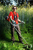Cute gardener with lawn mower — Stock Photo
