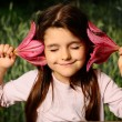 Girl put your ear flower, listen to the sounds of nature — Stock Photo #48658757