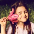 Girl put your ear flower, listen to the sounds of nature — Stock Photo #48658763