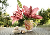 Fresh lilies in a glass of water on garden background — Stock Photo