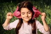 Girl put your ear flower, listen to the sounds of nature — Stock Photo