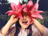 Cheerful girl playing with flowers, looking into the camera through the lily — Stock Photo