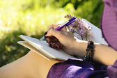 Notebook, pen and female hand close up, park — Stock Photo