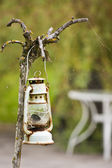 Old gas lamp on driftwood — Stock Photo