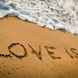 "Inscription ""love is..."" on sand — Stock Photo"