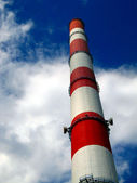 Red and white high chimney in the blue sky with white clouds — Stock Photo