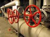 Pipes and valves with red knobs — Stock Photo