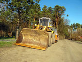 Bulldozer, road roller, earthmoving machinery and road construct — Stock Photo