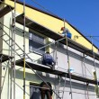 Stock Photo: Priming facade of building before applying plaster,