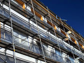 Detail of the facade of a large building at the insulating walls with visible scaffolding — Stock Photo