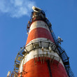 Stock Photo: High red-white concrete industrial chimney