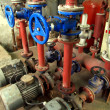 Stock Photo: Valves with blue handles and old pumps embedded