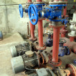 Stock Photo: Valves with blue handles and old pumps embedded in installat