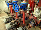 Valves with blue handles and old pumps embedded — Stock Photo