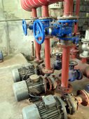 Valves with blue handles and old pumps embedded in the installat — Stock Photo