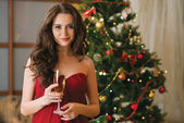 Girl with a glass of champagne on new year's tree — Stock Photo