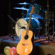 Acoustic Guitar and Drums on Stage - Stock Photo
