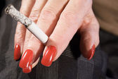 红色的指甲和燃烧的香烟 — 图库照片