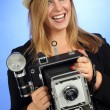 Fun blond female holding old camera — Stock Photo #12017277