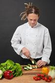 Chef with dreadlocks chopping — Stock Photo
