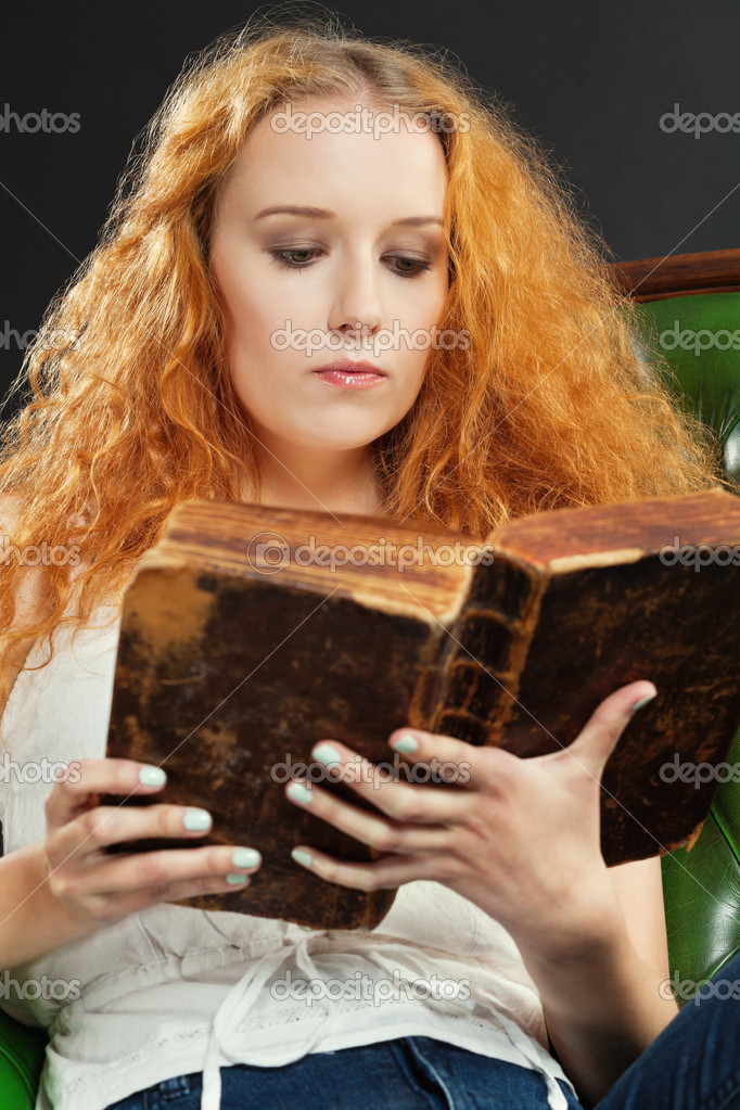 Photo of a female with red curly hair reading an old book.  Stock Photo #12253791
